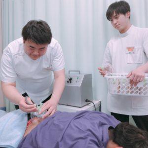 男性スタッフが男性の患者様に吸い玉治療を行なっている