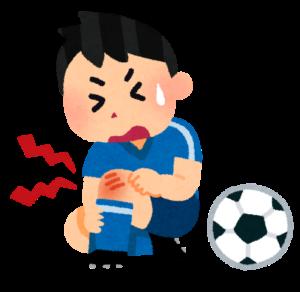 男の子がサッカー中に膝を痛めている