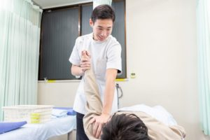 肩周りに施術を行うスタッフ